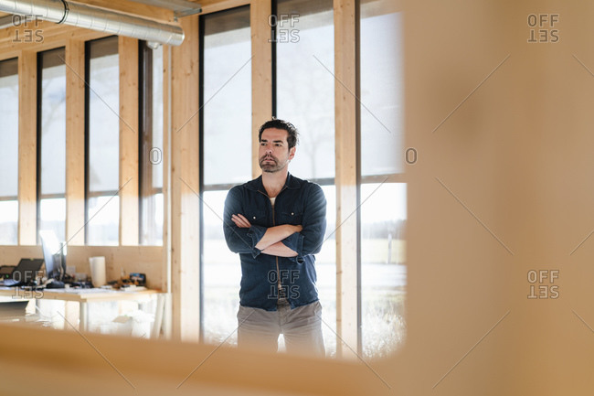 Businessman standing at the window in wooden open-plan office
