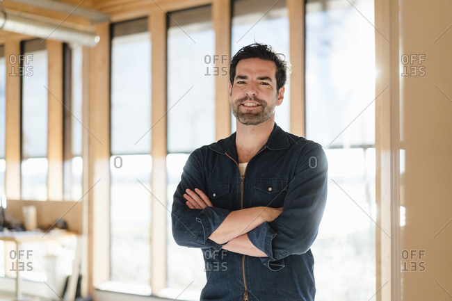 Portrait of smiling businessman standing at the window in wooden open-plan office