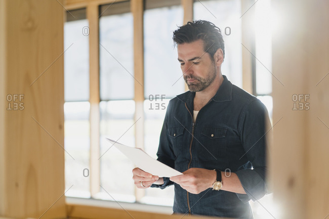 Businessman reading document in wooden open-plan office