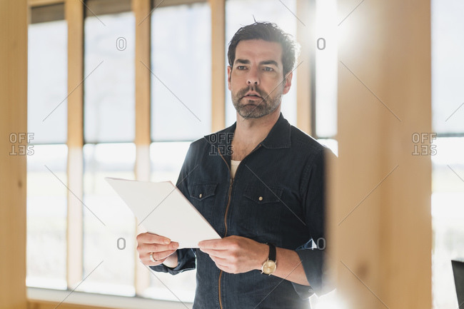 Businessman holding document in wooden open-plan office