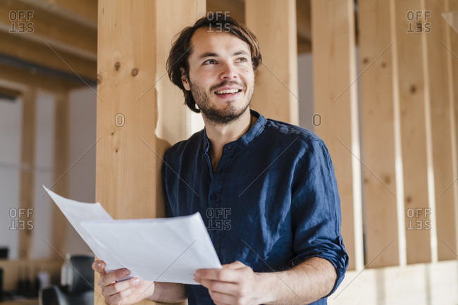 Smiling businessman holding documents in wooden open-plan office