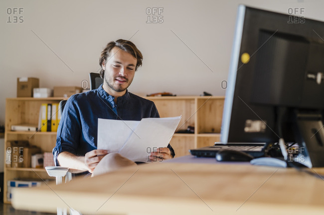 Businessman reading document at desk in wooden open-plan office
