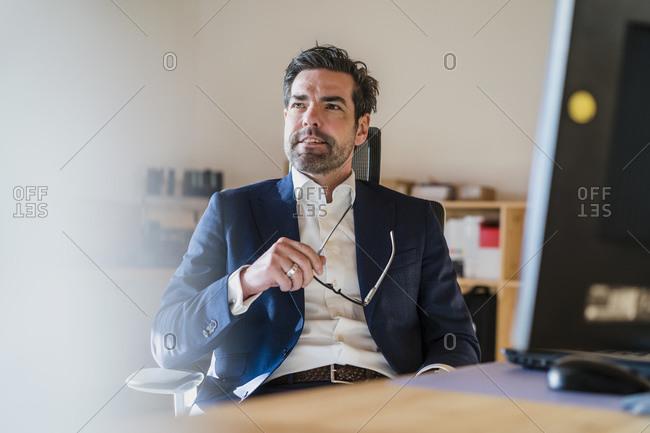 Portrait of businessman sitting at desk in wooden open-plan office