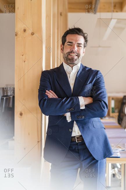 Portrait of confident businessman in wooden open-plan office