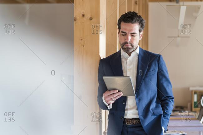 Businessman using tablet in wooden open-plan office