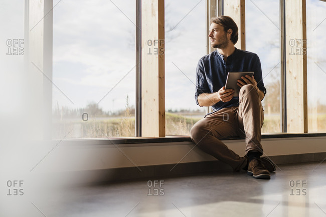 Businessman with tablet looking out of window in open-plan office
