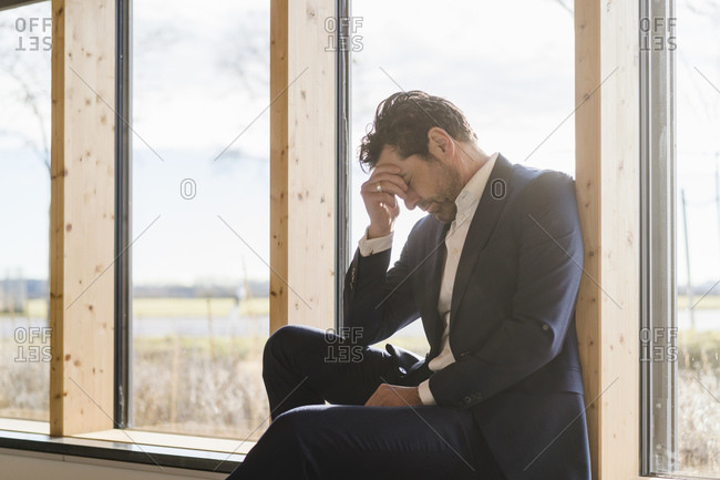 Tired businessman sitting at the window in office