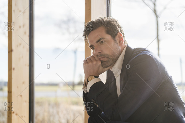 Serious businessman sitting at the window in office