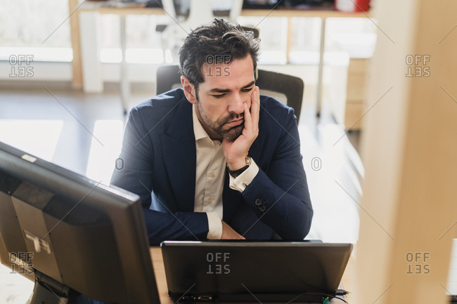 Frustrated businessman sitting at desk in office