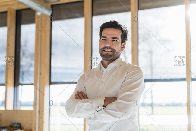 Portrait of confident businessman at the window in open-plan office