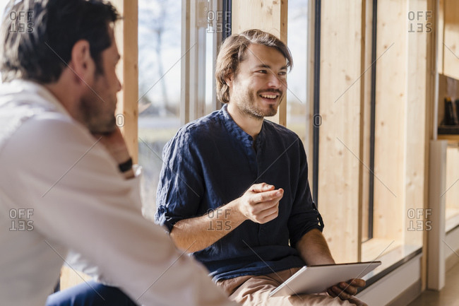 Two businessmen with tablet talking at the window in open-plan office