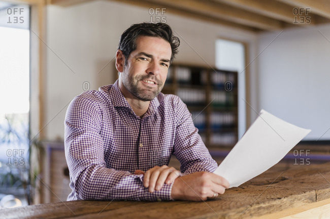 Portrait of smiling businessman with document in wooden open-plan office