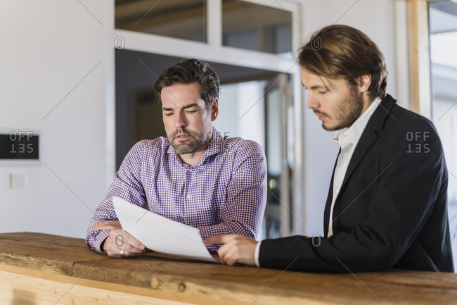 Two businessmen with documents talking in wooden open-plan office