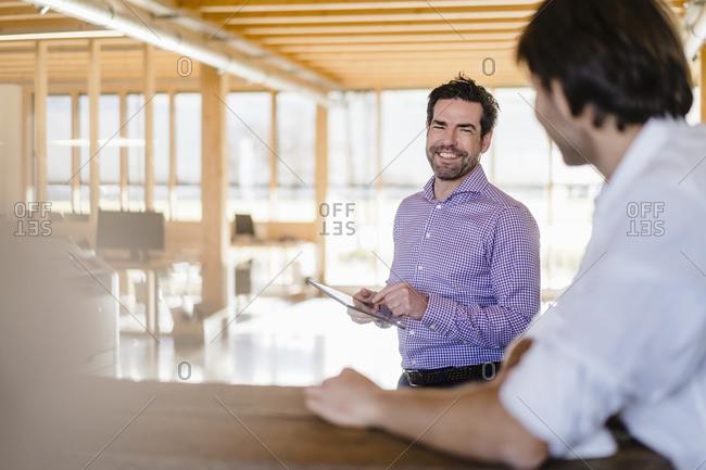 Two businessmen talking in wooden open-plan office