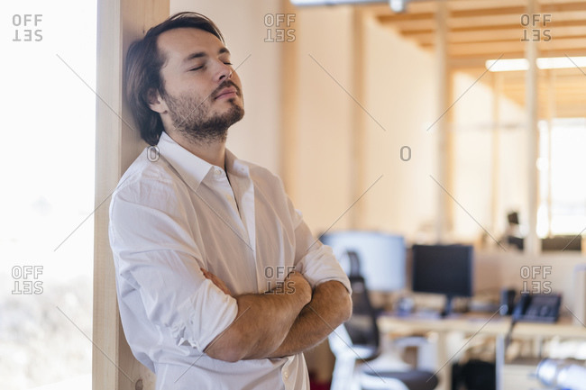 Businessman with closed eyes leaning against beam in wooden open-plan office