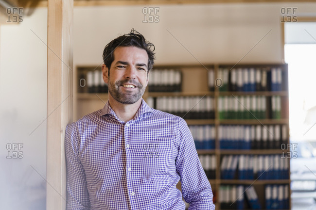 Portrait of smiling businessman leaning against beam in wooden open-plan office
