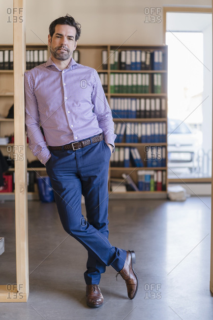 Portrait of confident businessman leaning against beam in wooden open-plan office