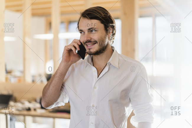 Businessman on the phone in wooden open-plan office