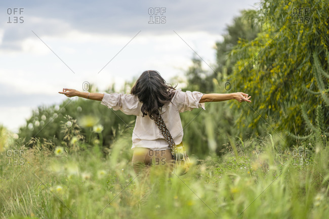 Rear view of carefree young woman with arms outstretched and head back standing on green plants- Alicante- Alicante Province- Spain