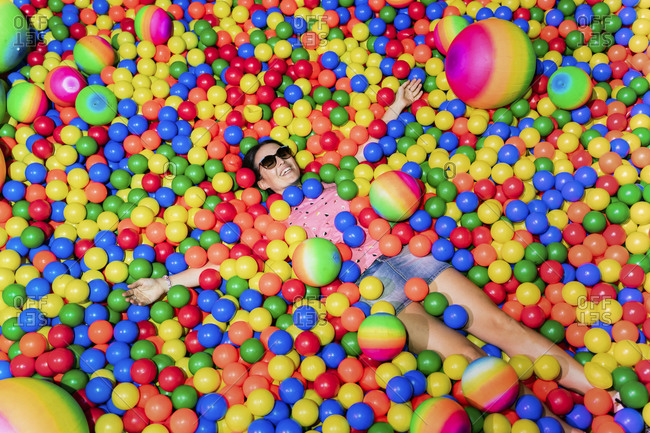 Portrait of happy woman lying among many colorful balls
