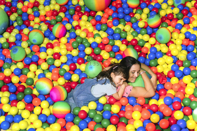 Happy woman lying with her little daughter among many colorful balls