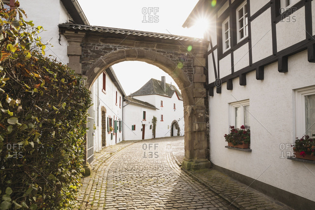 Germany- North Rhine-Westphalia- Refreshed- Sun shining over archway in empty cobblestone alley