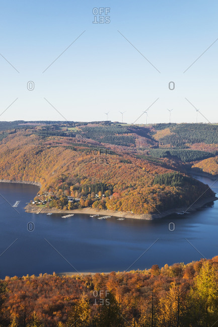 Germany- North Rhine-Westphalia- Rur Reservoir in autumn with wind turbines in distant background