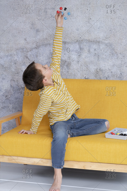 Boy is playing and experimenting with molecular models sitting on yellow couch