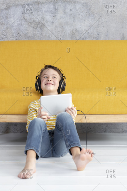 Boy playing with tablet and wearing headphones at a yellow couch
