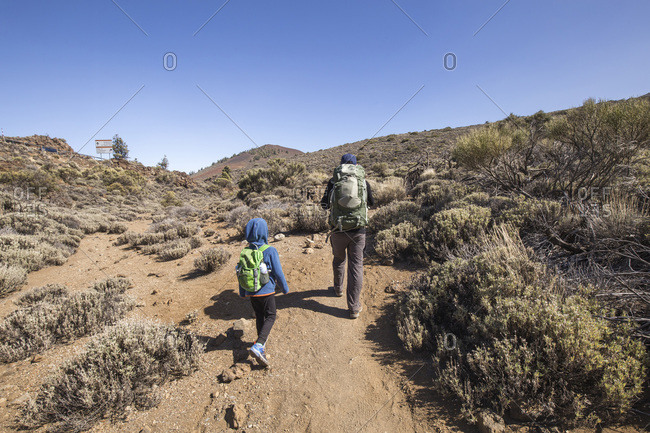 A father and his son trekking in the Arenas Negras area- Teide National Park- Tenerife- Spain
