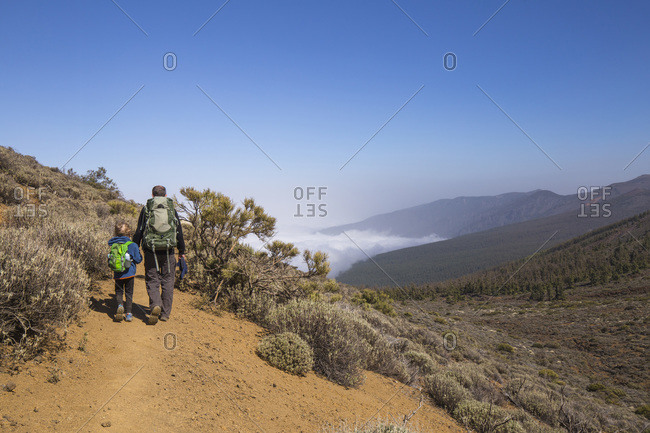 Rear view of a father with his son trekking in the Arenas Negras area- Teide National Park- Tenerife