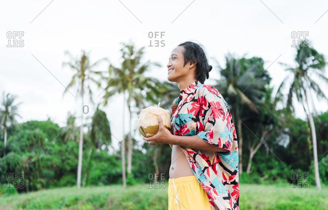 Happy man enjoying fresh coconut water- Borneo Island- Malaysia