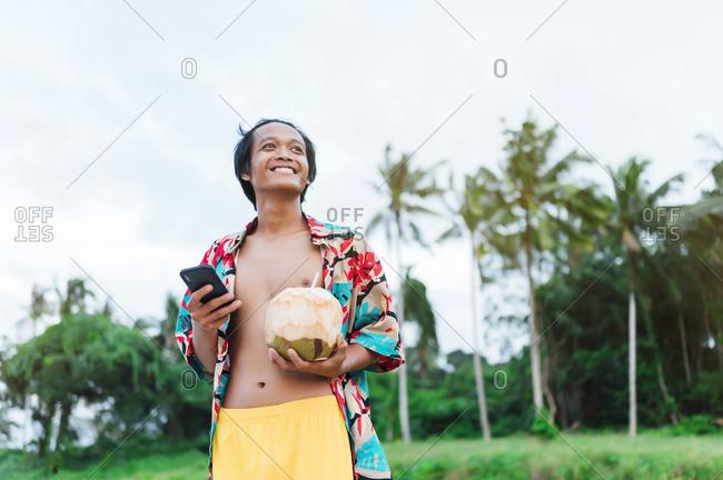 Portrait of happy man with smartphone and fresh coconut- Borneo Island- Malaysia