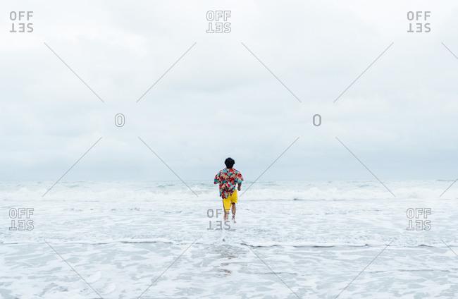 Back view of man running into the sea- Borneo Island- Malaysia