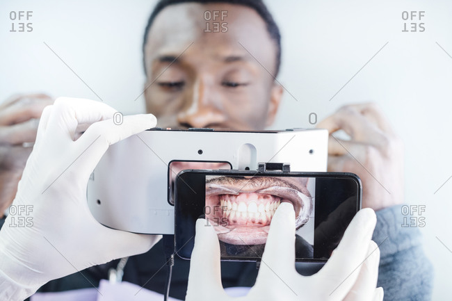 Dentist taking photo of teeth with special photographic apparatus