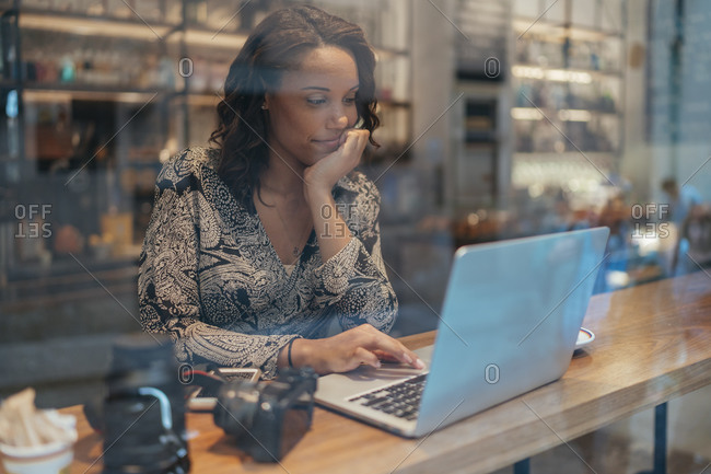 Young woman with a camera using laptop in a cafe behind windowpane