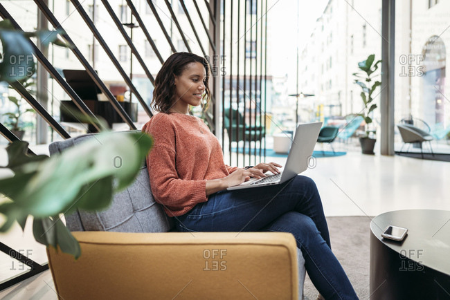 Young woman using laptop in a foyer