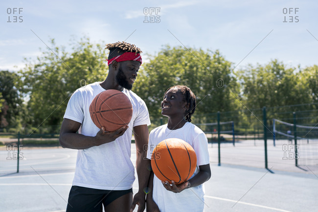 Father and son with basketball on basketball court