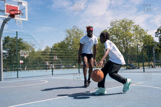 Father and son playing basketball on basketball court