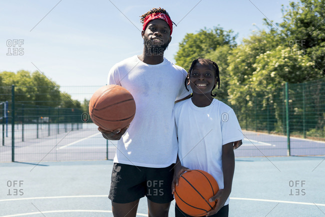Father and son with basketballs on basketball court