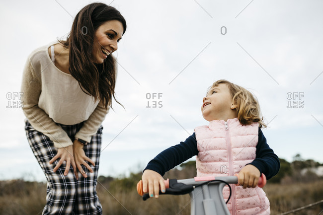 Happy mother looking at daughter with balance bicycle