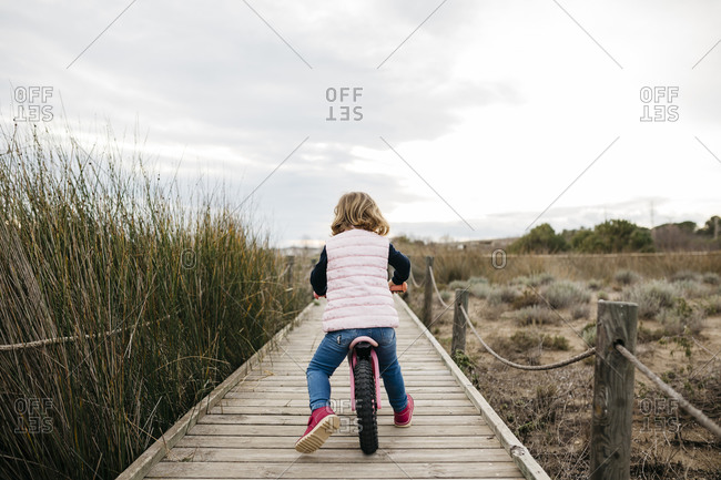 Rear view of toddler girl with balance bicycle on a boardwalk in the countryside