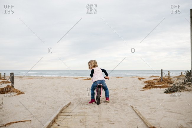 Rear view of toddler girl with balance bicycle on a boardwalk in the dunes