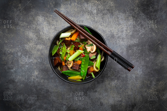 Pair of chopsticks and bowl of ready-to-eat miso soup with udon noodles- tofu- sugar snap peas- paprika- carrots-†mu-err mushrooms- scallion and cilantro