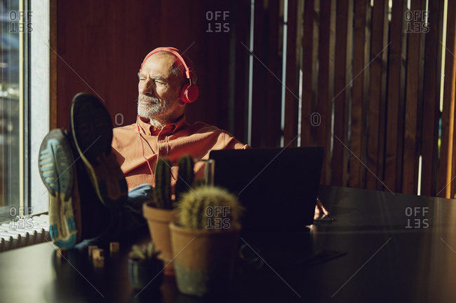Relaxed businessman taking a break- listening music with headphones in his sustainable office