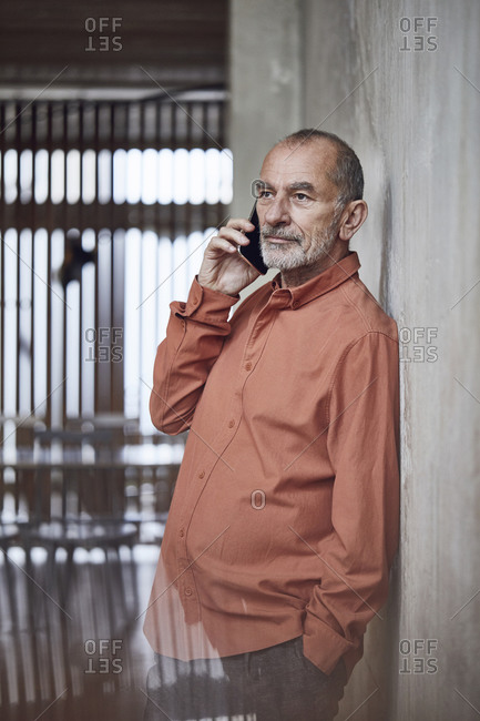 Creative businessman talking on the phone in his minimalistic office