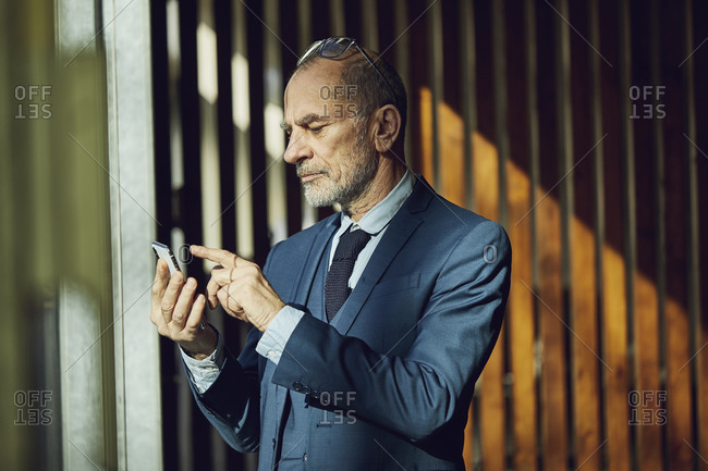 Senior businessman standing in his sustainable office- using smartphone
