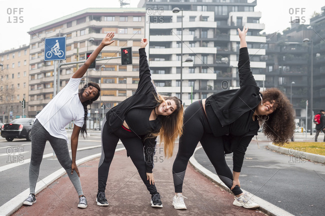 Three sportive young women training in the city