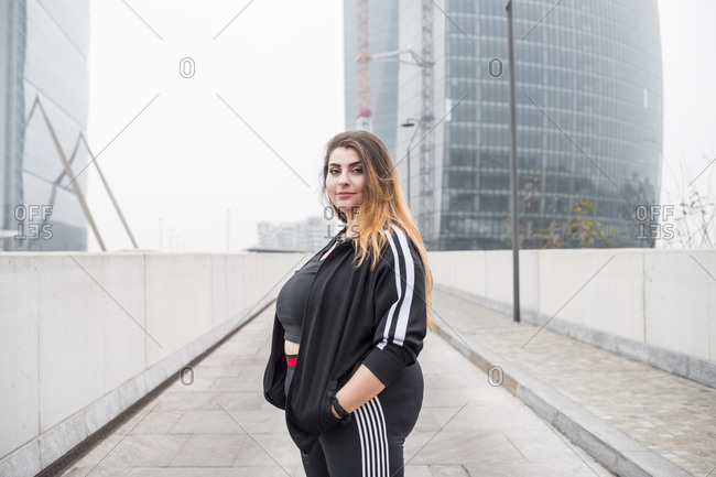 Plus size sportive young woman posing in the city