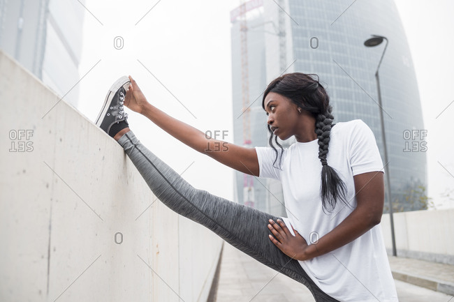 Sportive young woman stretching in the city